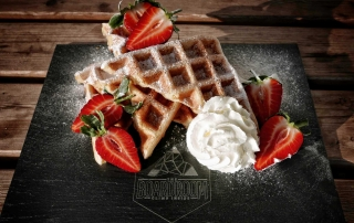 Freshly made waffles with strawberries and cream