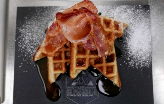 Freshly made waffles with bacon and maple syrup